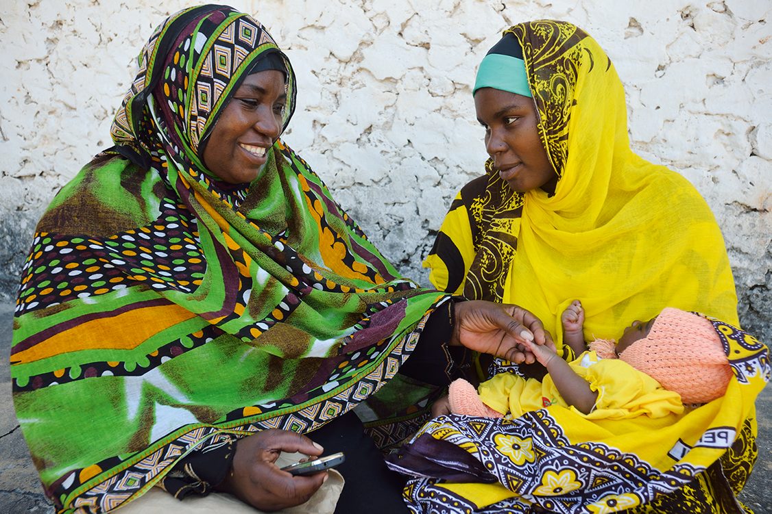 A community health volunteer in Zanzibar, guided by a mobile phone tool, counsels a new mother